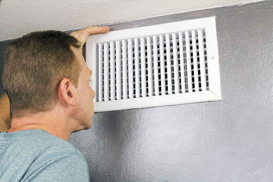 Homeowner inspects grille register of central HVAC system